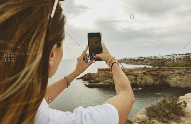 Back view of anonymous female tourist in casual clothes and sunglasses taking pictures on smartphone while standing on rocky cliff on seashore on cloudy day in Ibiza