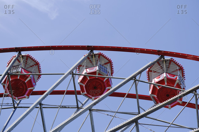 From below of Ferris wheel with red cabins located on amusement park on sunny day with blue sky