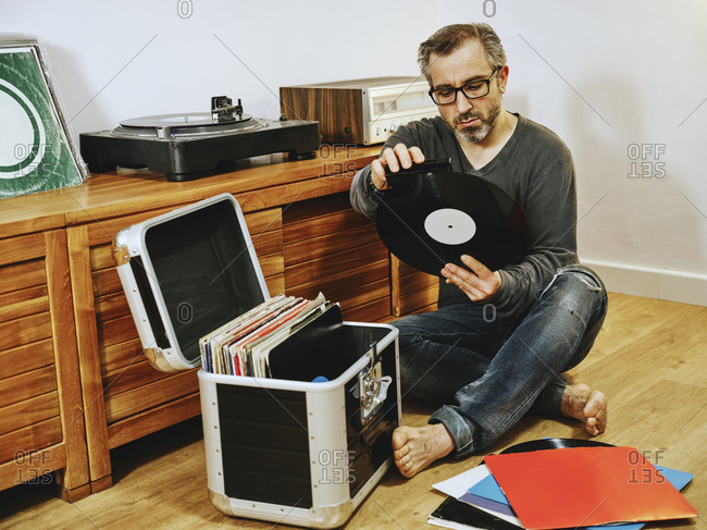 Stylish male wearing casual clothes and eyeglasses sitting on wooden floor and picking vinyl record while enjoying weekend at home