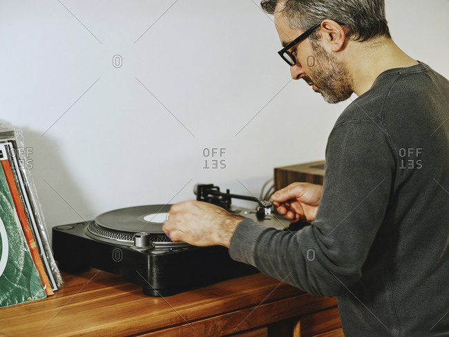 Side view of serious male setting turntable and enjoying songs on retro vinyl disc while chilling at home