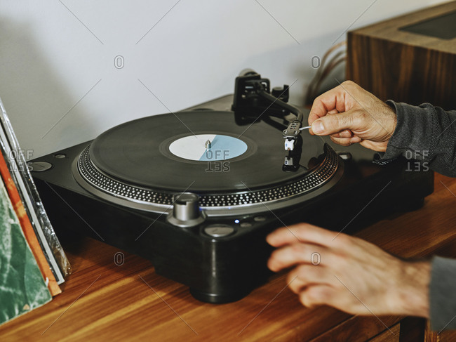 Cropped unrecognizable person setting turntable and enjoying songs on retro vinyl disc while chilling at home