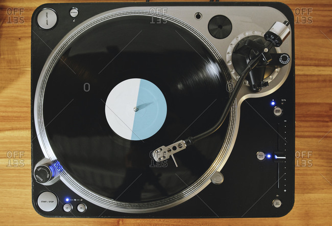 Top view of contemporary vinyl record player with retro disc placed on wooden table in living room