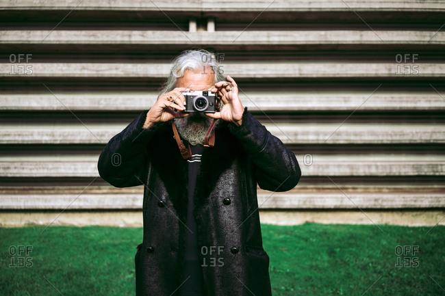 Elderly male in trendy clothes standing in city near urban building and taking pictures on retro photo camera