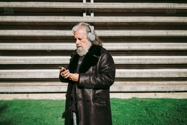 Serious male hipster with long gray hair standing in street on sunny day and enjoying songs in wireless headphones while using smartphone