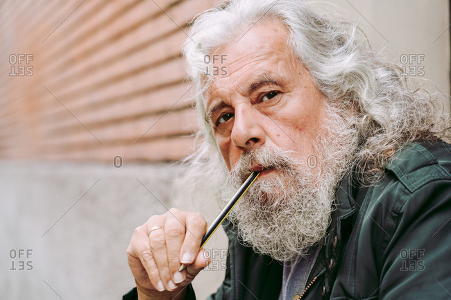 Pensive elderly male with long gray hair sitting on city street and pondering while looking at camera