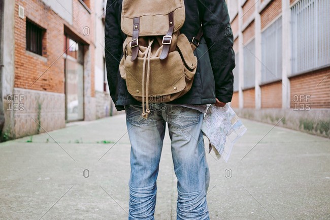 Back view of unrecognizable man in casual outfit carrying backpack and walking along street with map during journey in new city
