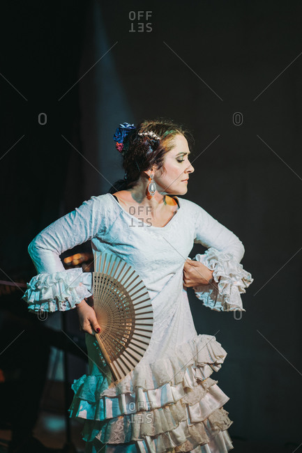 Hispanic female in ruffled dress and open hand fan dancing flamenco on theater platform behind black curtain and looking away