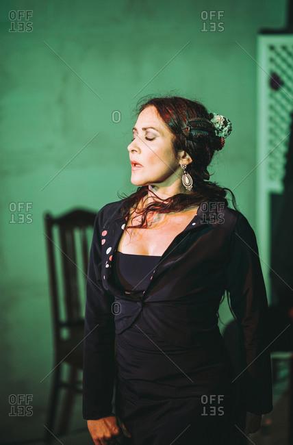 Hispanic female flamenco dancer acting on theater stage