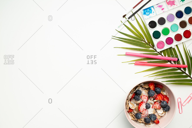 Top view of colorful paint palette and stationery placed on white background with bowl filled with muesli and fresh berries