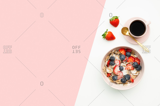 Top view of breakfast bowl with yummy muesli and berries placed on table with cup of coffee and fresh strawberries