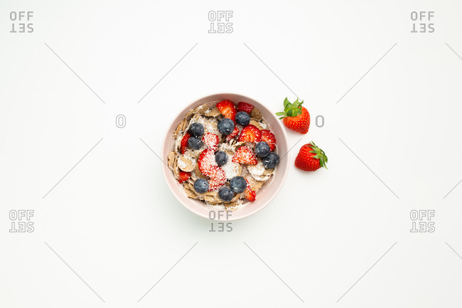 Top view of delicious dish with strawberries and blueberries placed on top of white table
