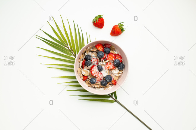 Top view of delicious dish with strawberries and blueberries placed on top of palm leaf