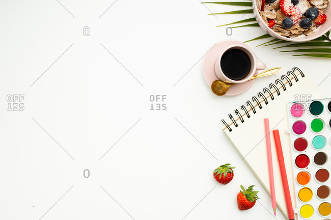 Top view of notebook with blank pages and colorful stationery placed on white desk with breakfast bowl and cup of morning coffee