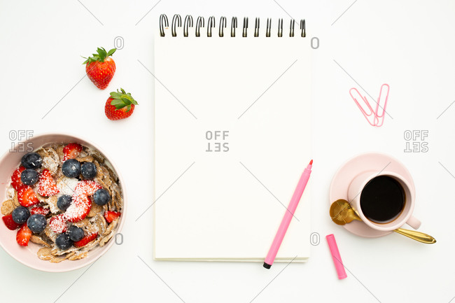 Top view of sketchbook and pink felt pen placed on table with strawberries and mug of hot coffee