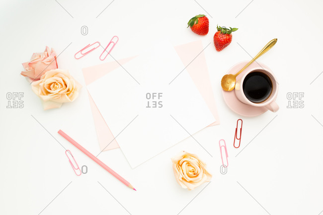 Top view of blank paper and stationery placed on white desk with hot espresso and rose buds as decoration