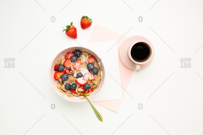 Top view of paper and stationery placed on white background with cup of aromatic coffee and delicious breakfast bowl in morning