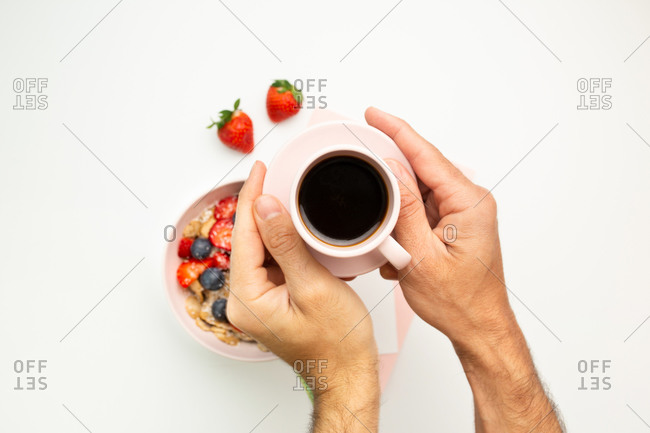 Top view of unrecognizable male sitting at white table with hot beverage and bowl with fresh berries while taking notes on paper