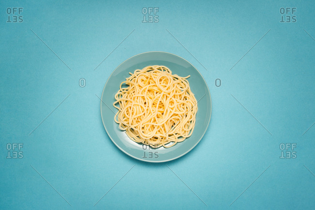 From above of blue ceramic plate with homemade cooked pasta on bright blue background