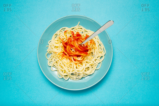 Top view of blue ceramic plate with pasta and tomato sauce on light blue background
