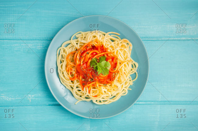 Top view of blue ceramic plate with pasta and tomato sauce decorated with parsley on light blue wooden background