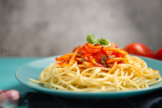 Blue ceramic plate with pasta and tomato sauce decorated with parsley and basil served between cloves of garlic and couple of tomato on light blue background