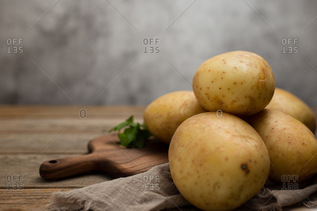 Raw potatoes placed on wooden cutting board near linen cloth and green parsley on wooden table against gray background