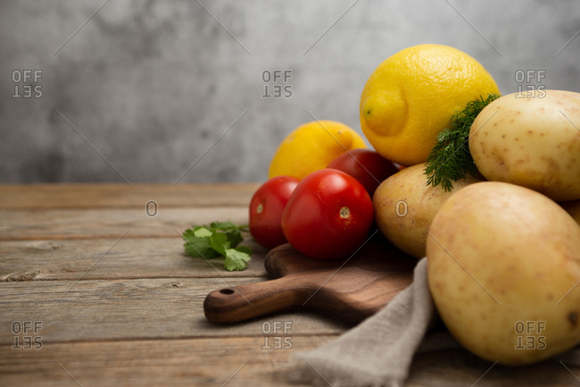 Composition of different raw vegetables placed on wooden cutting board near linen cloth and various greens on wooden table against gray background