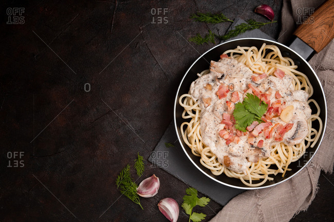 Composition of tasty spaghetti with ham slices and mushrooms in creamy sauce cooked in pan and placed on wooden cutting board at dark table with garlic and gray linen fabric aside