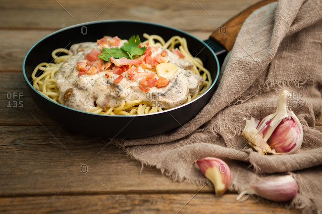 From above tasty spaghetti with ham slices and mushrooms in creamy sauce cooked in pan and placed on wooden cutting board at a wooden table with garlic and linen fabric aside