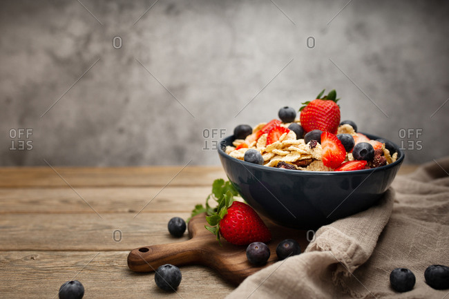 From above delicious breakfast bowl of corn flakes with strawberries and blueberries placed on cutting board and decorated with linen cloth and berries around dish on wooden table with gray background