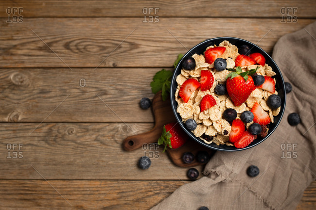 Top view of delicious breakfast bowl of corn flakes with strawberries and blueberries placed on cutting board and decorated with linen cloth and berries around dish on wooden background