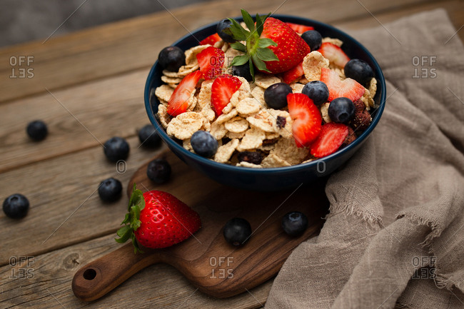 From above delicious breakfast bowl of corn flakes with strawberries and blueberries placed on cutting board and decorated with linen cloth and berries around dish on wooden background