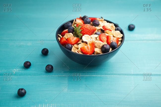 From above delicious breakfast bowl of corn flakes with strawberries and blueberries placed on cutting board and decorated with linen cloth and berries around dish on wooden blue background