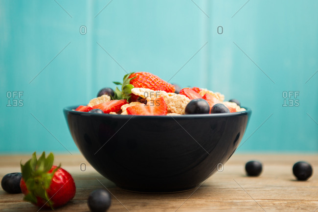 From above delicious breakfast bowl of corn flakes with strawberries and blueberries placed on cutting board and decorated with linen cloth and berries around dish on wooden table with blue background
