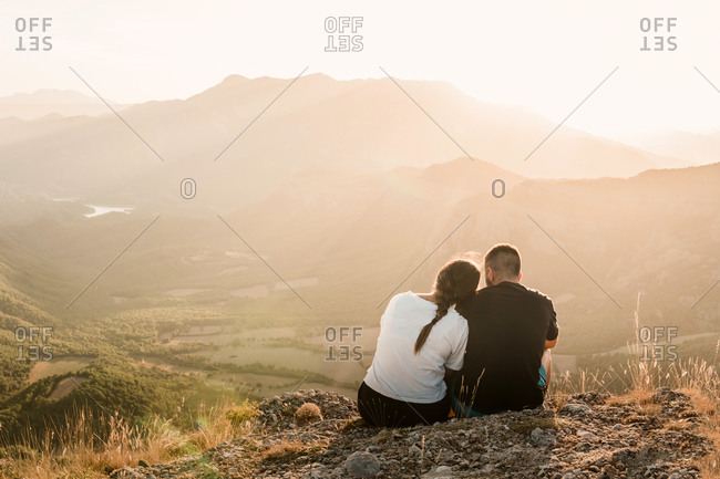 Back view of romantic couple of tourists in casual clothes sitting on stone edge of cliff embracing and enjoying picturesque landscape during sunny day