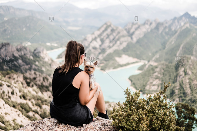 Back view of anonymous female tourist in casual black clothes and sunglasses sitting with dog on rocky hill and admiring picturesque scenery in summer