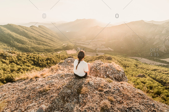 Back view of anonymous female tourist in casual clothes enjoying picturesque landscape while sitting on stony ground on sunny day in summer