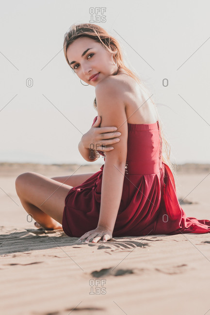 Attractive young lady with long blond hair wearing stylish red dress sitting on coast while looking at camera