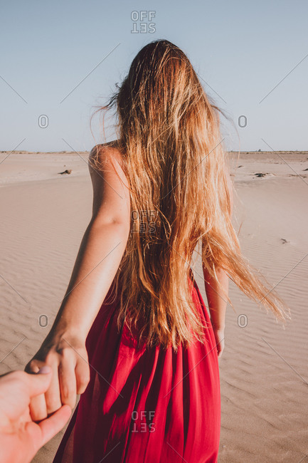 Back view of anonymous young lady with long blond hair wearing stylish red dress walking on sand towards camera and holding hand of anonymous person