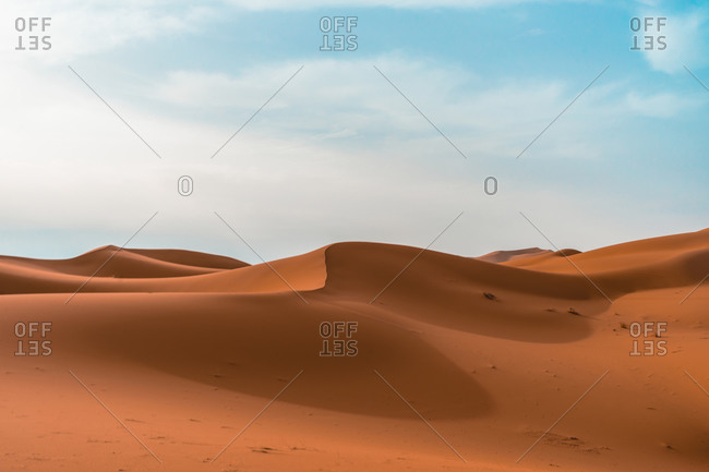 Minimalistic desert landscape with sandy dunes under blue cloudy sky in sunny day
