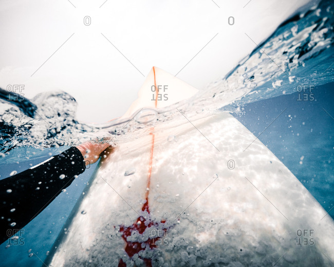 Unrecognizable person on surfboard sinking in clean sea water during ride near Fuerteventura Island, Spain
