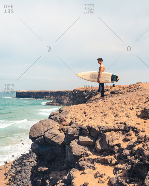 Side view of shirtless man with surfboard standing on stony coast and admiring waving sea on Fuerteventura Island, Spain