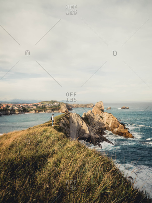 Distant side view of male traveler with backpack and camera standing on rocky seashore and admiring amazing seascape during trip in Spain