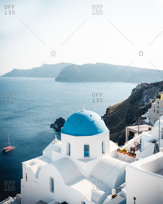 From above of famous blue white houses on picturesque rocky seashore with incredible views of clear calm sea in Santorini on hot summer day