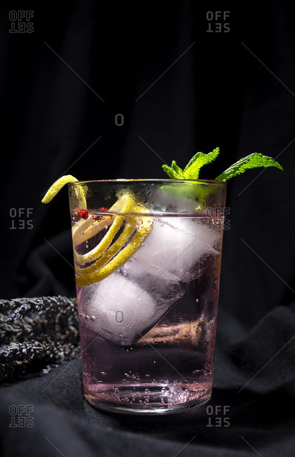 Gin tonic cocktail with pink tonic water, pink pepper, rosemary, mint, cinnamon, lemon and orange on dark background