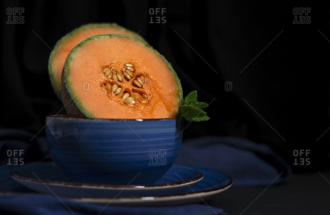 Fresh assortment melon with mint  on dark background. Vegan food concept. Healthy food