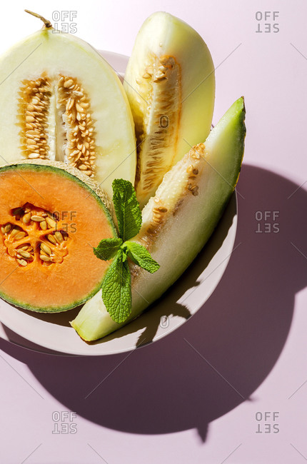 Fresh assortment melon with mint  on pink background with high contrast light. Vegan food concept. Healthy food