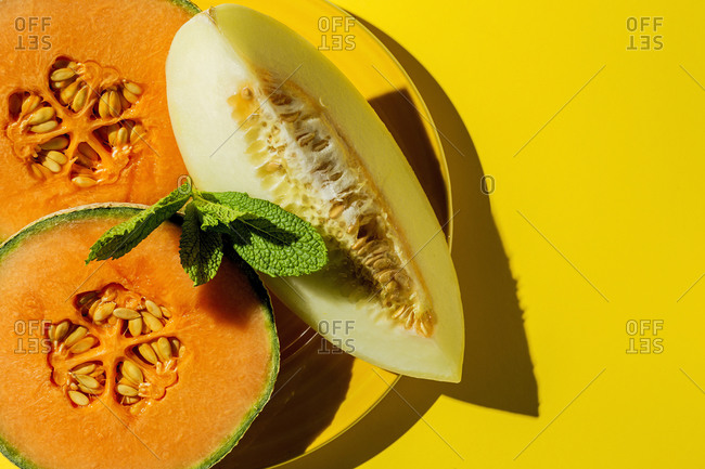 Fresh assortment melon with mint  on yellow background with high contrast light. Vegan food concept. Healthy food