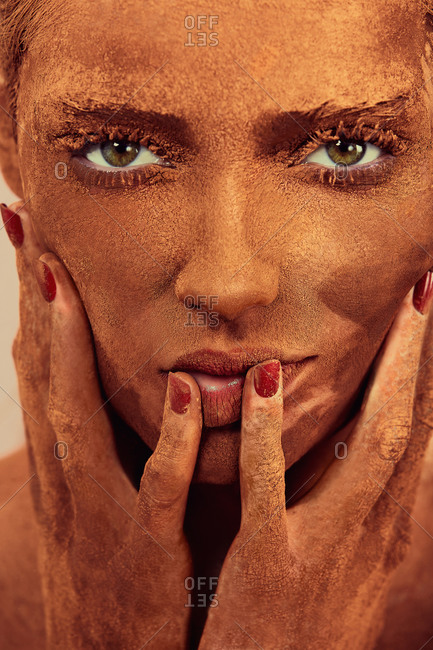 Young beautiful woman with chocolate powder on face touching skin and looking at camera