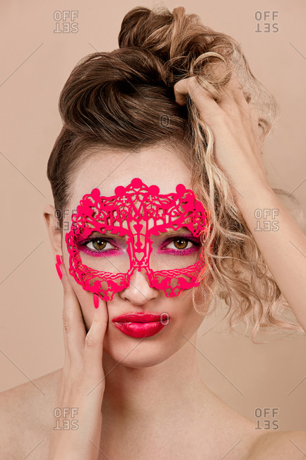 Young woman with vivid makeup and in ornamental mask touching face and grasping hair against beige background